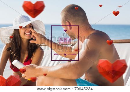 Handsome man applying sun cream on his girlfriends nose against valentines day greeting