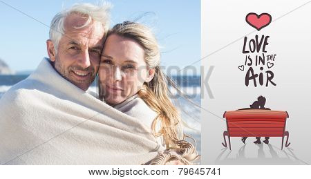 Smiling couple wrapped up in blanket on the beach against love is in the air
