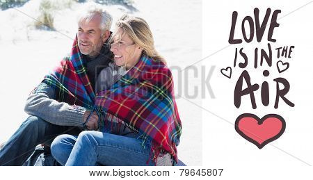 Happy couple wrapped up in blanket sitting on the beach against love is in the air