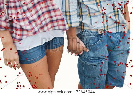 Couple in check shirts and denim holding hands against red love hearts
