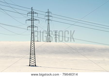 High Voltage Electricity Power Pylon On Snowy Field
