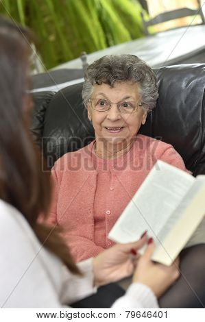Homecare reading book to elderly woman