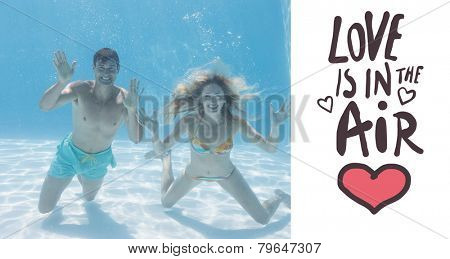 Cute couple smiling at camera underwater in the swimming pool against love is in the air