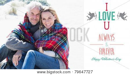 Happy couple wrapped up in blanket sitting on the beach against i love you message