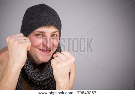 A shirtless man with scarf and hat