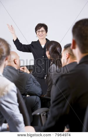 Hispanic Woman Speaking To Group Of Businesspeople