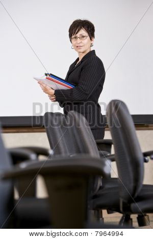 Mature Hispanic Business Woman Standing By Chairs