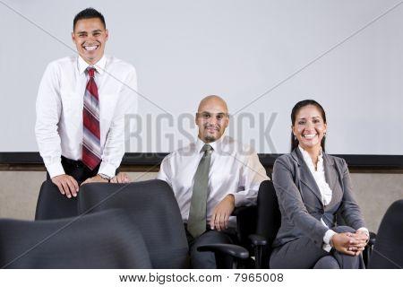 Three Hispanic Business Colleagues In Boardroom