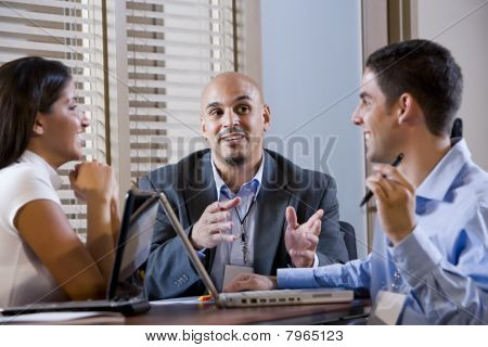 Three Office Workers Conversing At Desk