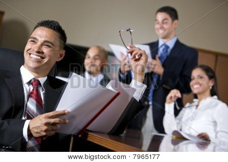 Hispanic Business People In Boardroom Smiling