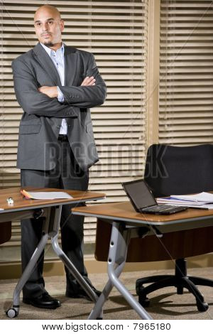Serious Hispanic Businessman Standing In Office