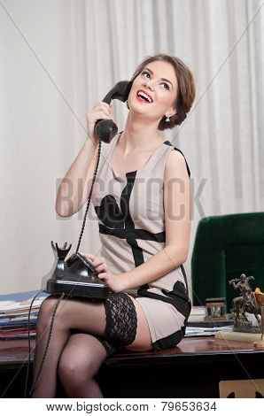 Happy smiling attractive woman wearing an elegant dress and black stockings talking by phone