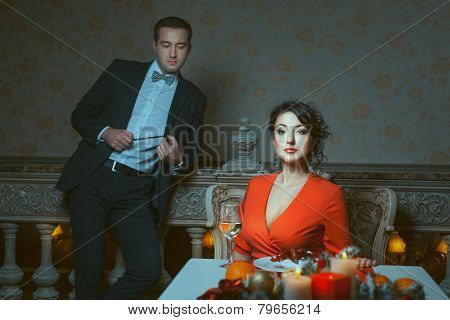 Woman Sitting, Man Standing Out Of Focus.