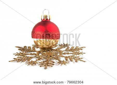 Christmas bauble resting on a golden snowflake ornament, focus on the reflection on the bauble; with copy space