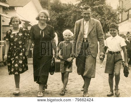 POLAND, CIRCA 1935: Vintage photo of parents with three children walking down the street