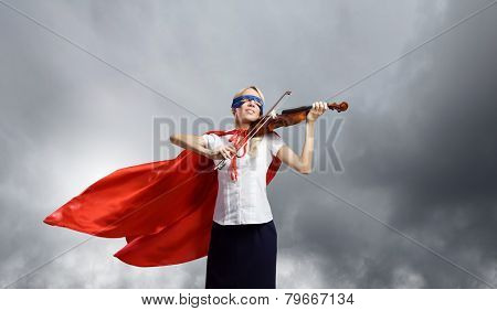Young woman in super hero costume playing violin