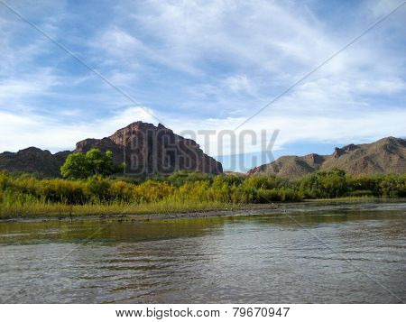 Desert River With Mountains In Background