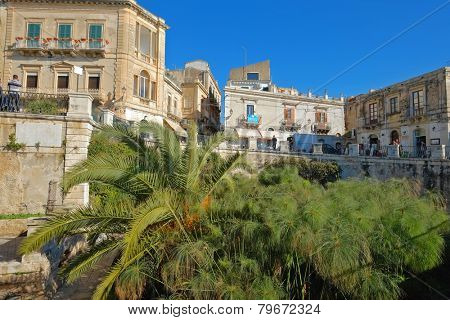 SIRACUSA, ITALY - JANUARY 03 2015,: Arethuse Fountain and baroque architecture in Ortigia Old Town of Siracusa, Sicily. Shot in 2015