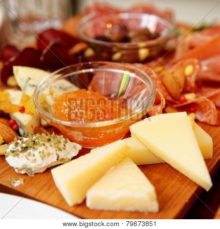 Cheese and sausage platter with nuts and citrus jam