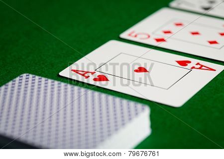 casino, gambling, poker, and entertainment concept - close up of playing cards on green table surface