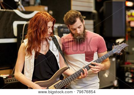 music, sale, people, musical instruments and entertainment concept - happy couple of musicians with bass guitar at music store