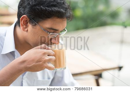 Asian Indian businessman sipping a cup hot milk tea during lunch hour at cafeteria.