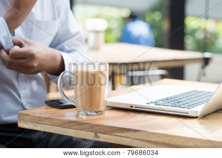 Asian Indian businessman having a cup hot milk tea and rolled up his sleeve during office break.