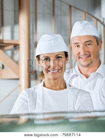 Portrait of confident male and female butchers smiling in butchery