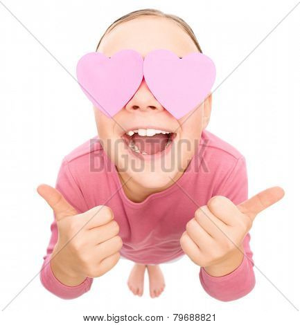 Little girl is holding hearts over her eyes and showing thumb up sign, fisheye portrait, valentine concept, isolated on white