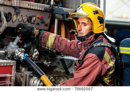 Fireman Controlling Water Pressure At Truck.