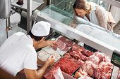 pic of slaughterhouse  - High angle view of male butcher showing meat to female customer at butchery - JPG
