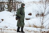 foto of cold-war  - RUSSIA LIZLOVO - DECEMBER 14: Unidentified German soldier walking on reenactment of the counterattack under the Moscow in 1941 in World War II in Moscow region Lizlovo village Russia 2014 ** Note: Visible grain at 100%, best at smaller sizes - JPG