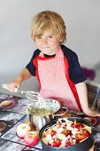picture of pie-in-face  - Adorable little toddler child helping and baking apple pie in home - JPG