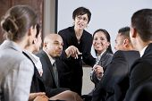 stock photo of motivation talk  - Diverse group of businesspeople conversing with woman standing at front - JPG