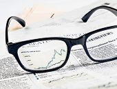 stock photo of newspaper  - financial chart and graph of stock indexes see through glasses lens on financial newspaper business concept - JPG
