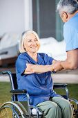 picture of male nurses  - Happy senior woman being assisted by male nurse to get up from wheelchair at nursing home yard - JPG