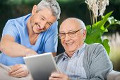 stock photo of nurse  - Happy male nurse and senior man enjoying while using tablet computer in nursing home porch - JPG