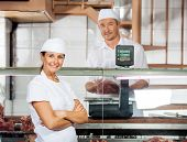 foto of slaughterhouse  - Portrait of confident female butcher with male colleague weighing meat at shop - JPG