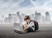 image of school building  - Smiling child sitting in front of a laptop with cityscape on the background - JPG