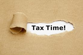 stock photo of irs  - The phrase Tax Time appearing behind torn brown paper - JPG