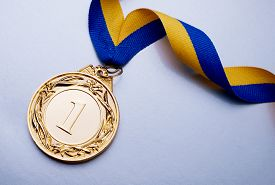 stock photo of gold medal  - Gold medal in the foreground on yellow blue ribbon - JPG