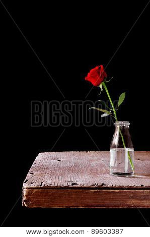 a red rose in a glass vase placed on a rustic wooden table, over a black background