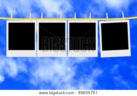 Old Photo Cards Hung With Wooden Hangers Over Blue Sky