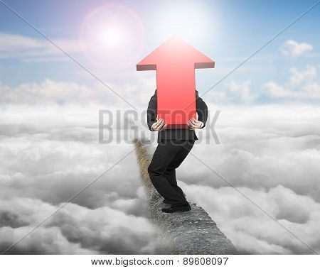 Businessman Carrying Red Arrow Sign On Ridge With Sunlight Cloudscape