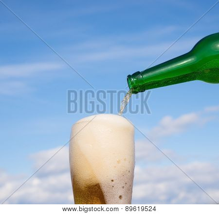 Someone fill glass with beer on blue  background