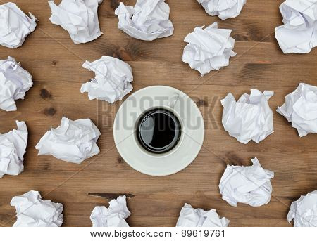 Cup of coffee paper sheets  and crumpled wads on table