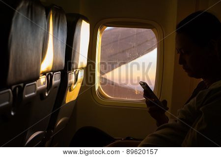 Undefined Traveler Holding Smart Phone In The Airplanes