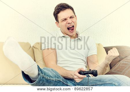 Young Man Playing Video Games With Joypad Or Joystick To Console Or Pc