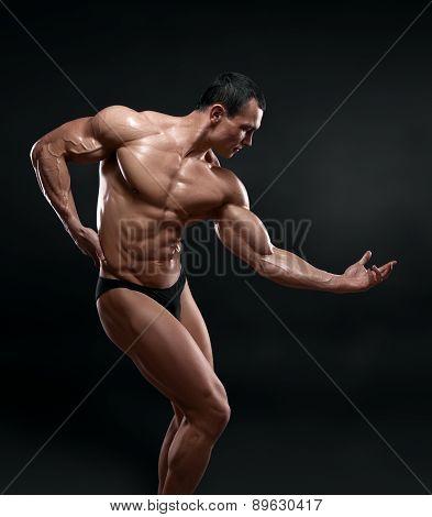 Handsome Muscular Bodybuilder Posing Over Black Background.