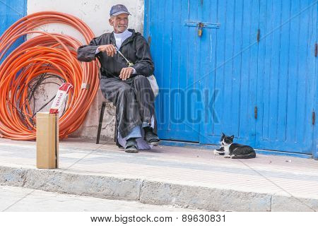 AS-SAWIRA, MOROCCO, APRIL 7, 2015: Elderly man sells cigarettes sitting in company of his cat